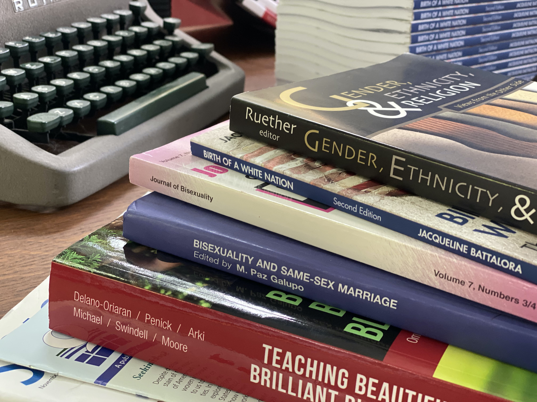 photo of stack of books reading: Ruether editor Gender, Ethnicity, & Religion, Birth of a White Nation, Journal of Bisexuality, Bisexuality and Same-Sex Marriage