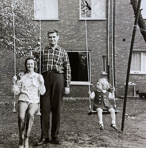 Black and white photo of a man standing behind a woman on an old fashion swing with his hand on her shoulder smiling while a toddler (Jacqueline Battalora) swings while looking at them infront of a brick building.