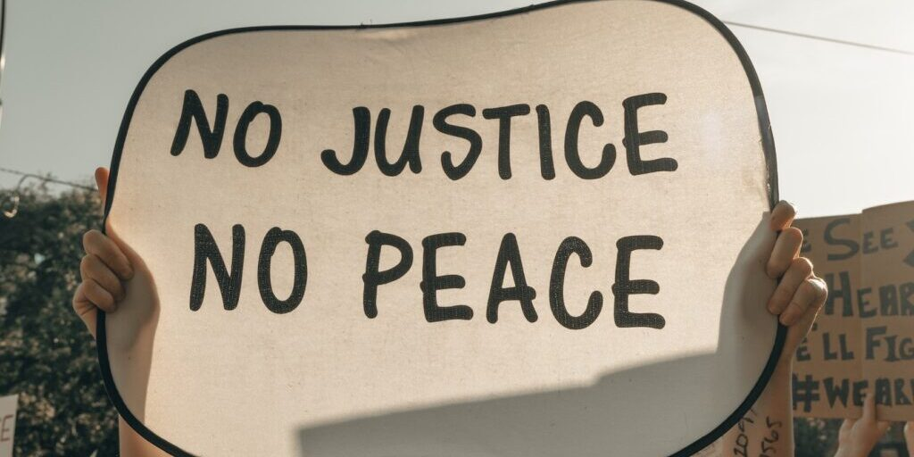 protestor holding a sign reading No Justice No Peace